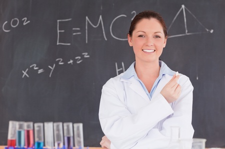 Young scientist holding a piece of chalk while standing in front of a blackboard photo