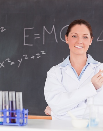 smilling: Smilling scientist standing in front of a blackboard looking at the camera Stock Photo