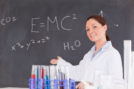 Cute scientist showing the equations on a blackboard photo