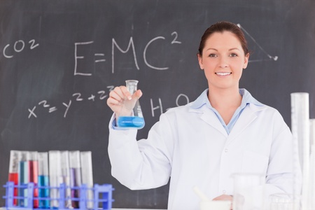 Cute scientist holding a container filled up with a blue liquid photo