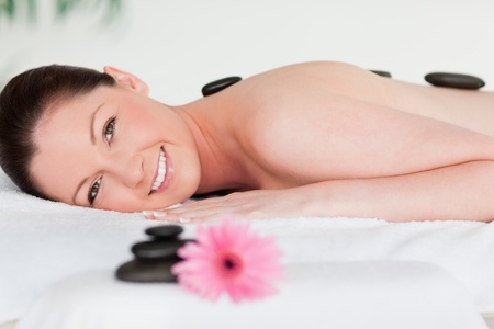 Happy young woman with massage stones and a pink gerbera photo
