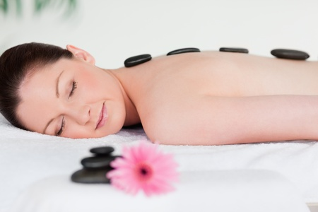 Young woman having a black stones massage photo