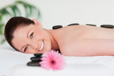 Happy young woman with a pink gerbera and massage stones with the camera focus on the woman photo