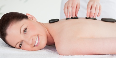 Smiling woman receiving a hot stone massage Stock Photo - 10217155
