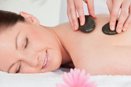 Young woman closing her eyes while having a hot stone massage Stock Photo - 10220074
