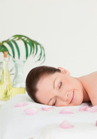 Portrait of a young woman lying on a massage table with petals photo