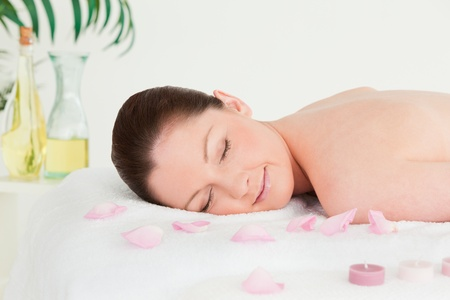 Beautiful woman lying on a massage table with petals and unlighted candles photo