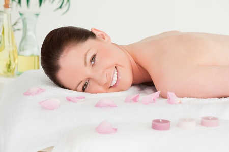 Smiling young woman lying on her belly with petals and unlighted candles photo
