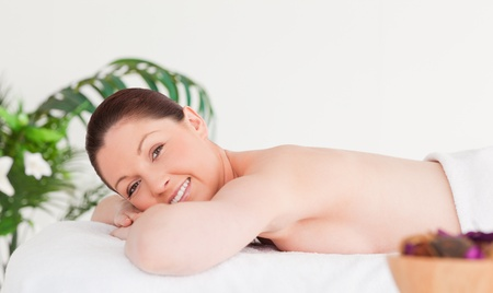 Young woman on a massage table smiling at the camera photo