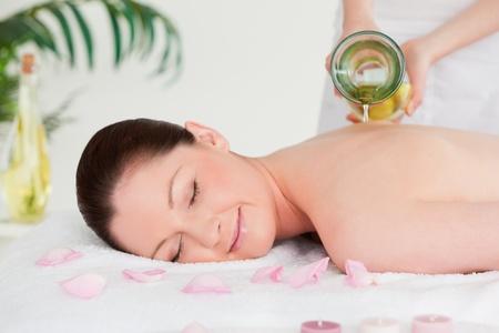 Masseuse Pourring massage �l auf einer jungen Frau wieder in einem spa