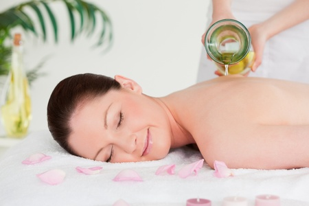 pour: Masseuse pourring massage oil on a young womans back in a spa