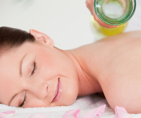 Smilling young woman having masssage oil versed on her back in a spa photo
