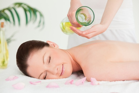 oil massage: A woman eyes closed getting massage oil on her back in a spa Stock Photo