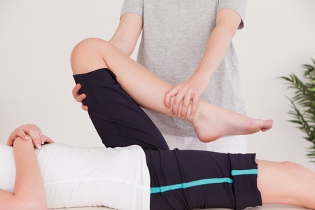 physical pressure: Masseuse stretching the leg of a youn woman Stock Photo
