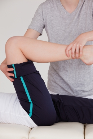Portrait of a masseuse stretching the right leg of an athletic woman photo