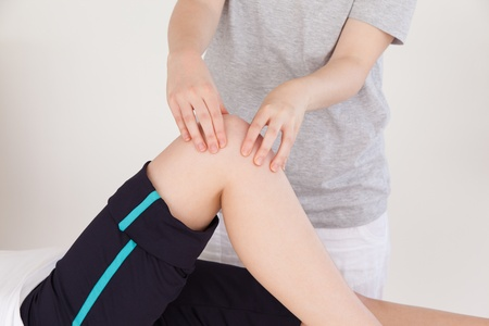 Close up of a masseuse massing the knee of an athletic woman photo