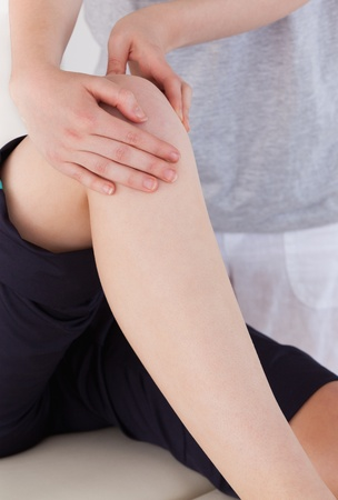 Portrait of a masseuse massing the knee of an athletic woman photo