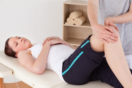 strength therapy: Masseuse massing the knee of a cute woman
