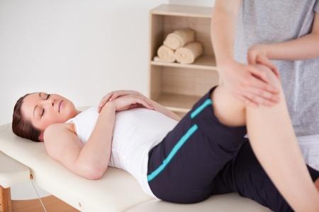 masaje deportivo: Masajista formaci�n la rodilla de una hermosa mujer