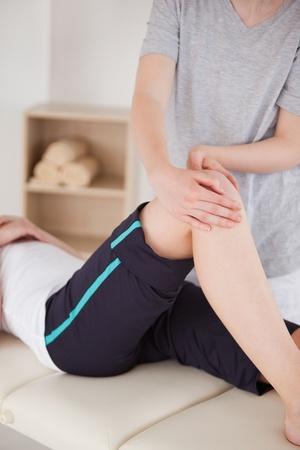 fysiotherapie: Portret van een sportvrouw met een knie-massage Stockfoto