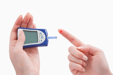 Close up of a blood glucose meter utilization photo