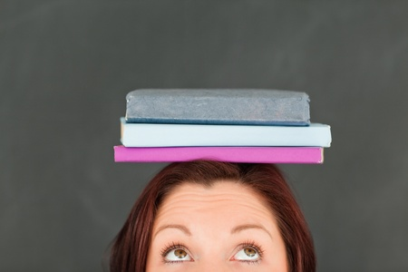 Young caucasian wearing books on her head with the camera focused on the top of the head in a classroom photo