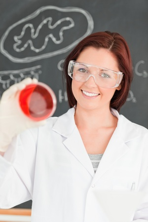 Smiling red-haired scientist looking at a petri dish in a classroom photo