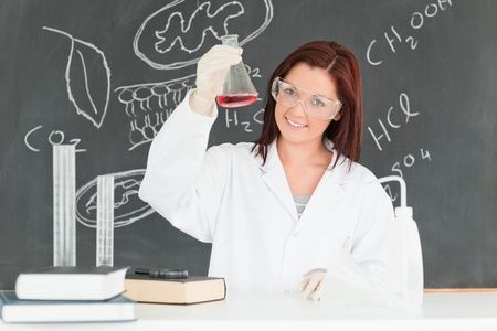 Young scientist showing a conical flask in a classroom Stock Photo - 10220473