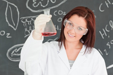 Close up of a cute scientist showing a conical flask in a classroom photo