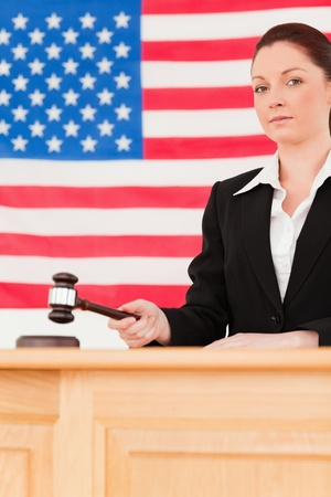Portrait of a serious judge knocking a gavel with an American flag in the background photo