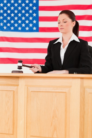 Focused judge knocking a gavel with an American flag in the background photo