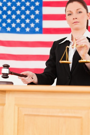 Portrait of a young judge knocking a gavel and holding scales of justice with an American flag in the background photo
