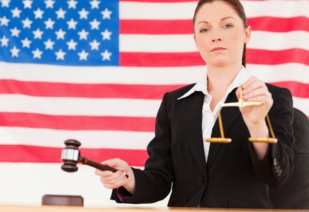 Close up of a cute judge knocking a gavel and holding scales of justice with an American flag in the background photo