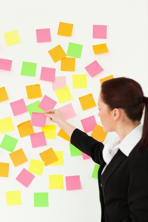 post it notes: Woman putting colourful repositionable notes on a white wall against a white background