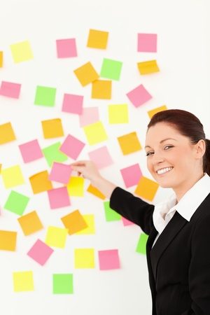 Smiling woman putting repositionable notes on a white wall against a white background photo