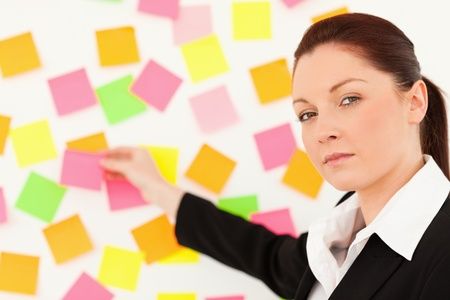 Responsible woman putting repositionable notes on a white wall photo