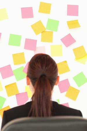 Redhead Frau schaut auf eine Wand voller repositional Hinweise auf eine wei�e Wand