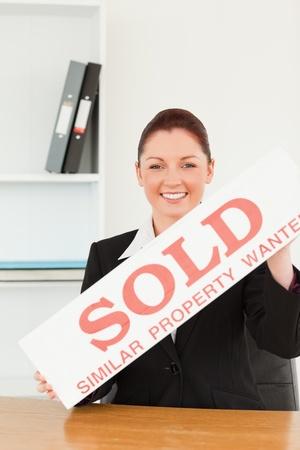 commercial real estate: Joven agente inmobiliario sosteniendo una pancarta vendida en su Oficina Foto de archivo