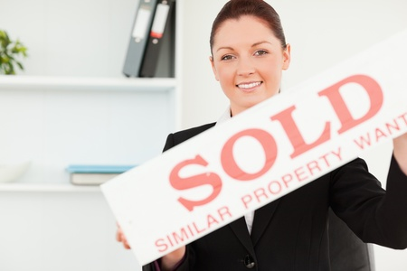 Beautiful real estate agent holding a sold placard in her office photo
