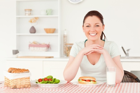 Good looking woman ready to eat a sandwich for lunch in her kitchen photo