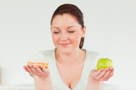 Attractive woman posing while holding a donut and a green apple against a white background photo