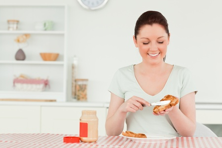 Good looking woman preparing a slice of bread and marmalade in the kitchen photo