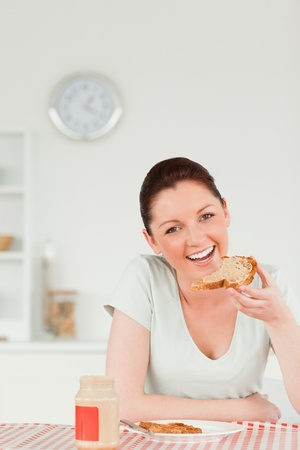 Good looking female preparing a slice of bread and marmalade in the kitchen photo
