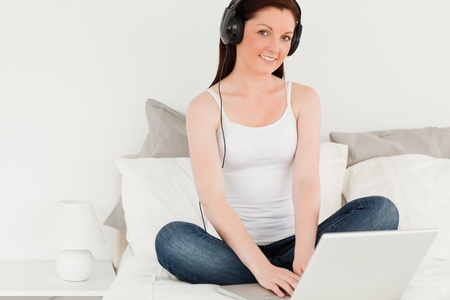 Good looking female relaxing with her laptop in her bedroom photo