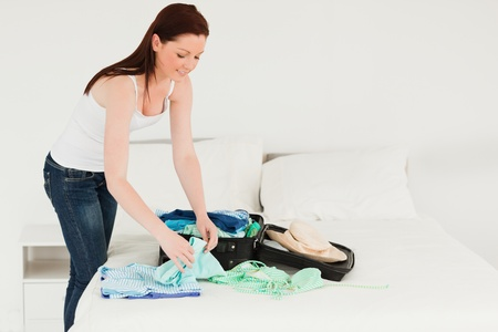 Beautiful woman packing her suitcase in her bedroom photo