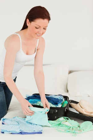 Attractive woman packing her suitcase in her bedroom photo