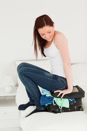 Attractive woman sitting on her suitcase in the bedroom photo
