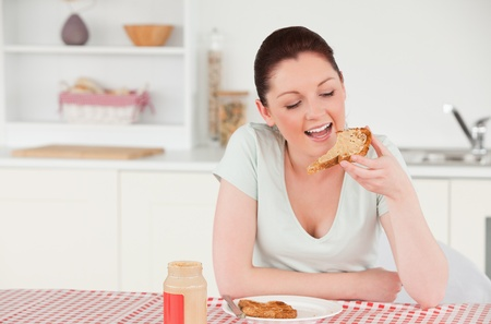 Attractive woman posing while eating a slice of bread in her kitchen photo