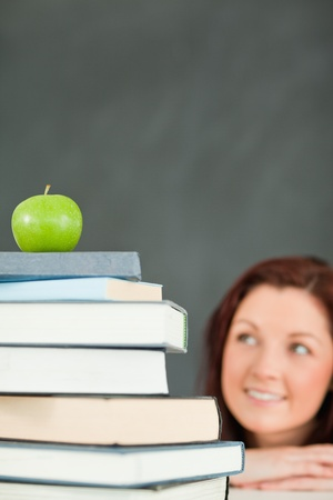Young student with a stack of books and an apple with the camera focus on the objects in a classroom photo