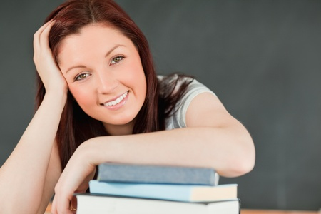 Close up of a smiling young student with her forearm on her books in a classroom photo